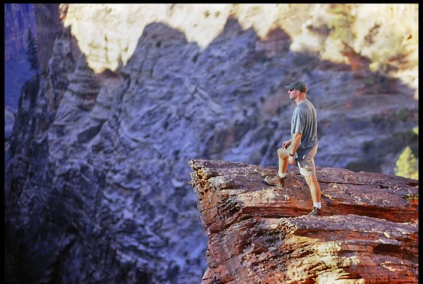 A hiker stands on a cliff overlooking Zion Canyon in Zion National Park as lead photo for a daily Bible devotional