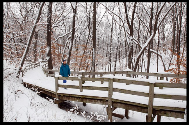 A woman walking on a snow covered boardwalk at Fontenelle Forest