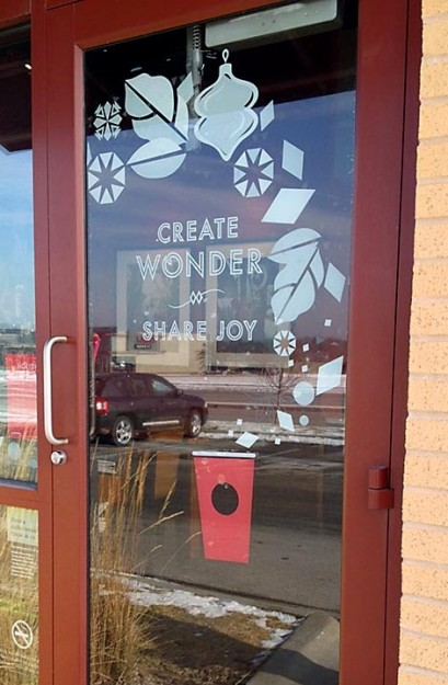 "A Starbucks Coffee door with the phrase ""Create Wonder and Share Joy""."