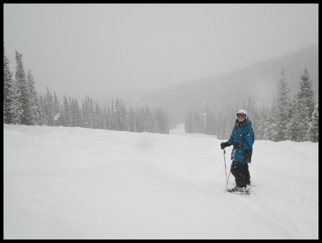 A woman skiing in heavy snowfall at Copper Mountain