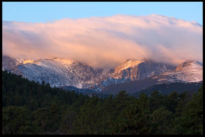 Clouds hang over a mountain in Rocky Mountain National Park, Colorado as the filtered mooring light strikes it.
