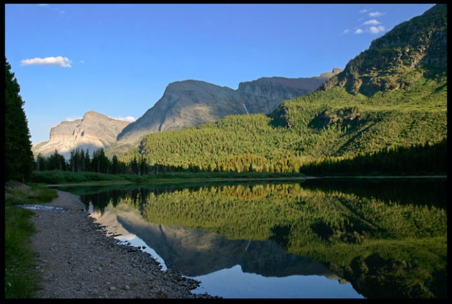 The mountains and trees surrounding trees reflect of a small lake in Glacier National Park