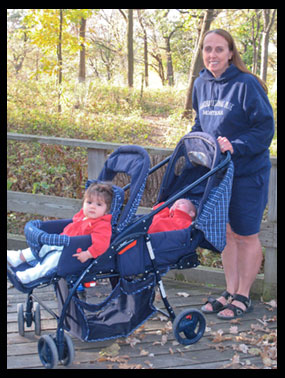 A woman pushes a double stroller with two infants in it on the Fontenelle Forest boardwalk.