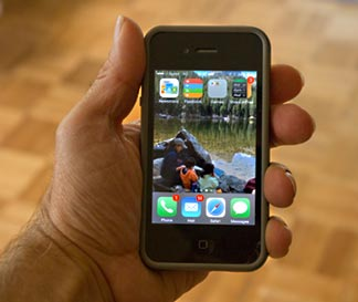 An iphone 4s with a photo of a mon and kids at Bear Lake in Rocky Mountain National Park