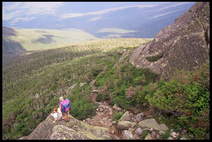 Two hikers on a rock over looking the Great Gulf Wilderness in the White Mountains of New Hampshire