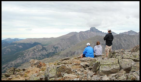 Hikers on top of Hallett Peak looking towards Longs Peak under light grey skies in Rocky Mountain National Park