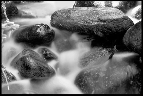 A black-and-white photograph of water flowing through the rocks of the Calypso cascade in Rocky Mount national Park