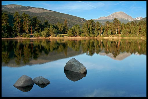 A mountain reflects in a still lake in Rocky Mountain National Park, Colorado. Should Christians embrace Creation care