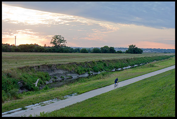 A lone cyclist riding a bike a sunset on the Keystone Trail, Nebraska