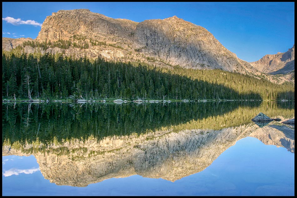 A surrounding mountains reflect in Cathedral Lake, Wyoming. Psalm 91:1 Shadow of the Almighty Bible verse