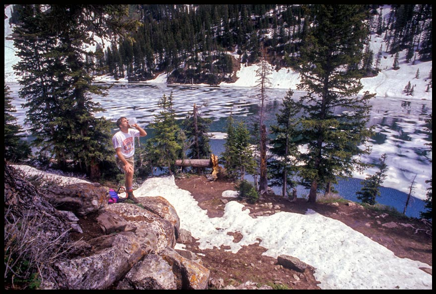 Hiker drinks water above a partially frozen Geneva Lake in the Colorado mountains and Bible verse Psalm 107 abut God's lovingkindness