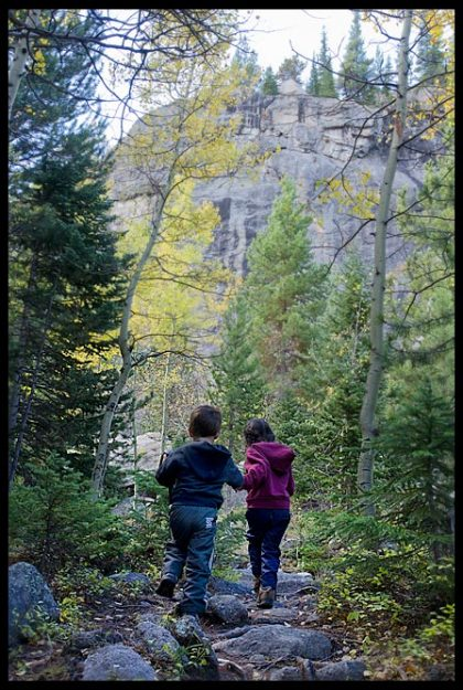 A little boy and girl hike a fall path near the Mills Lake Trail, Rocky Mountain National Park, Colorado and Matthew 18:3-4 Bible verse become like children