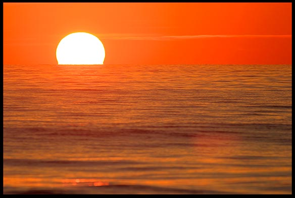 The sun sits on red horizon of water and sky at sunrise of the Melbourne, Florida coast. Does nature reveal any Biblical themes?
