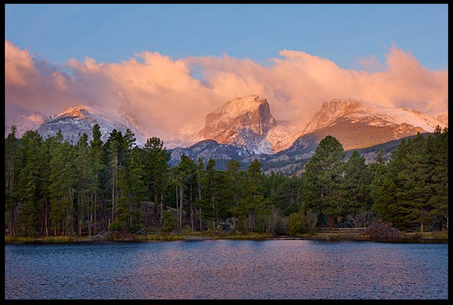 Sunrise strikes a red glow on the clouds and mountains above Sprague Lake in Rocky Mountain National Park, Colorado and Amos 4:13, He who forms mountains bible verse