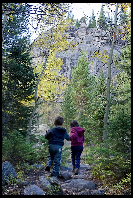 Children hike a trail toward yellow fall aspen trees near Mills Lake Trail, Rocky Mountain National Park, Colorado.