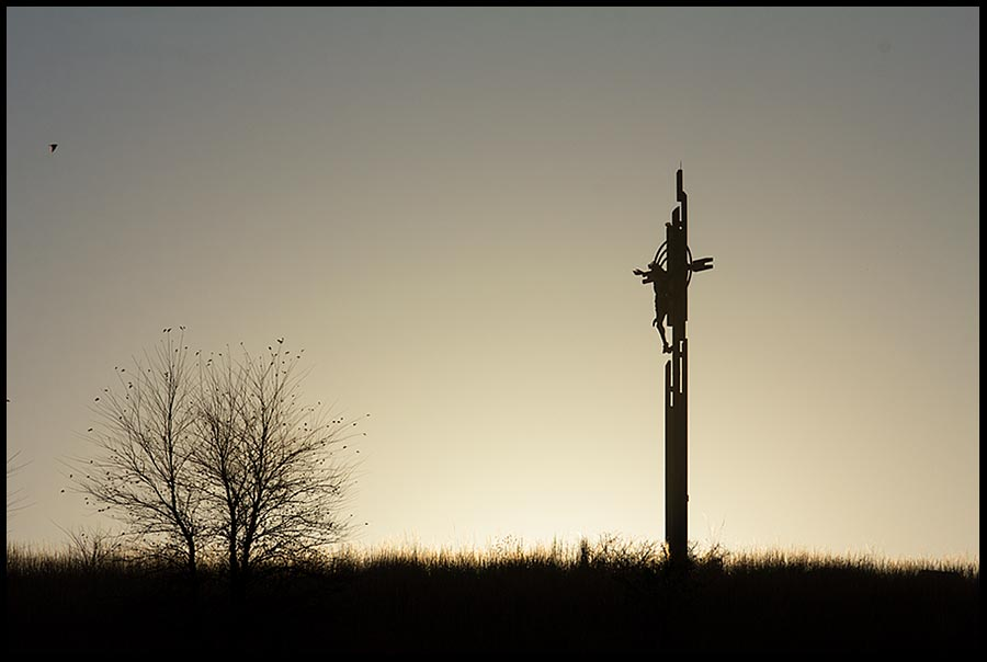 A silhouette of Christ on the cross at sunrise, Holy Family Shrine, Eastern Nebraska and Philippians 2:7-8 Bible verse reason for the season