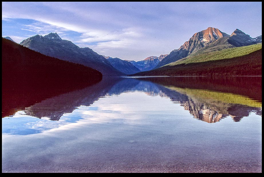 The surrounding mountain peaks reflect in Bowman Lake in Glacier National Park, Montana and Psalm 93:1 Bible verse robed in majesty