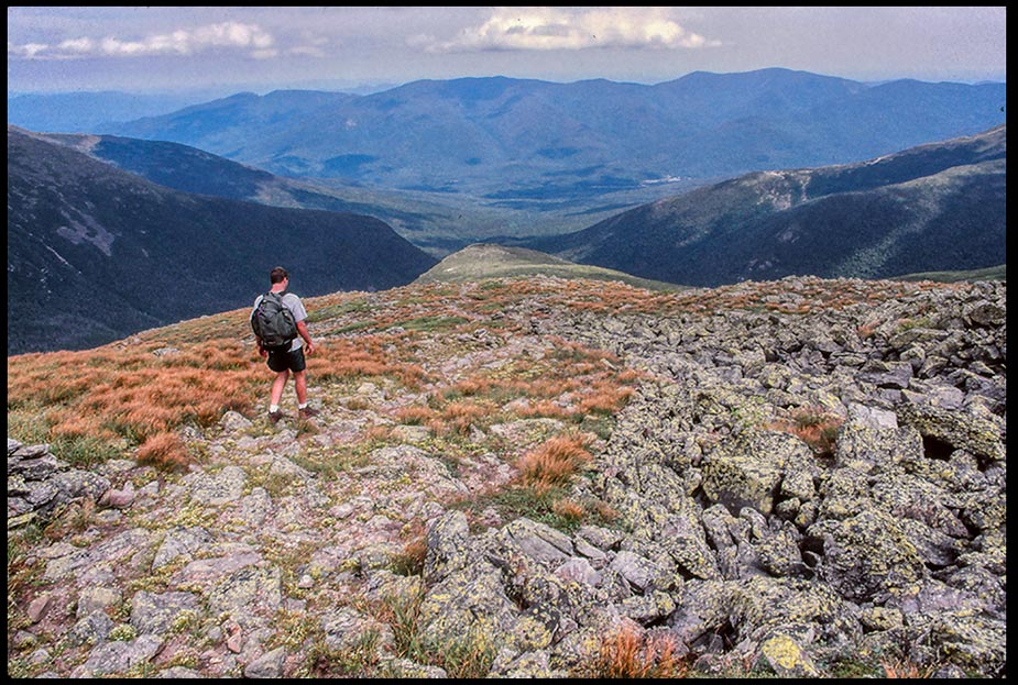 Hiker walks down a mountain in the White Mountains, New Hampshire and Psalm 119 Bible verse. Make me walk in the path