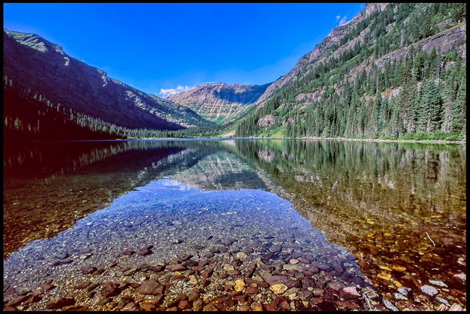 A mountain reflects through the rocky lake bottom of Arrow Lake, Glacier National Park, Montana. Bible verse Revelation 7:17 and water of life