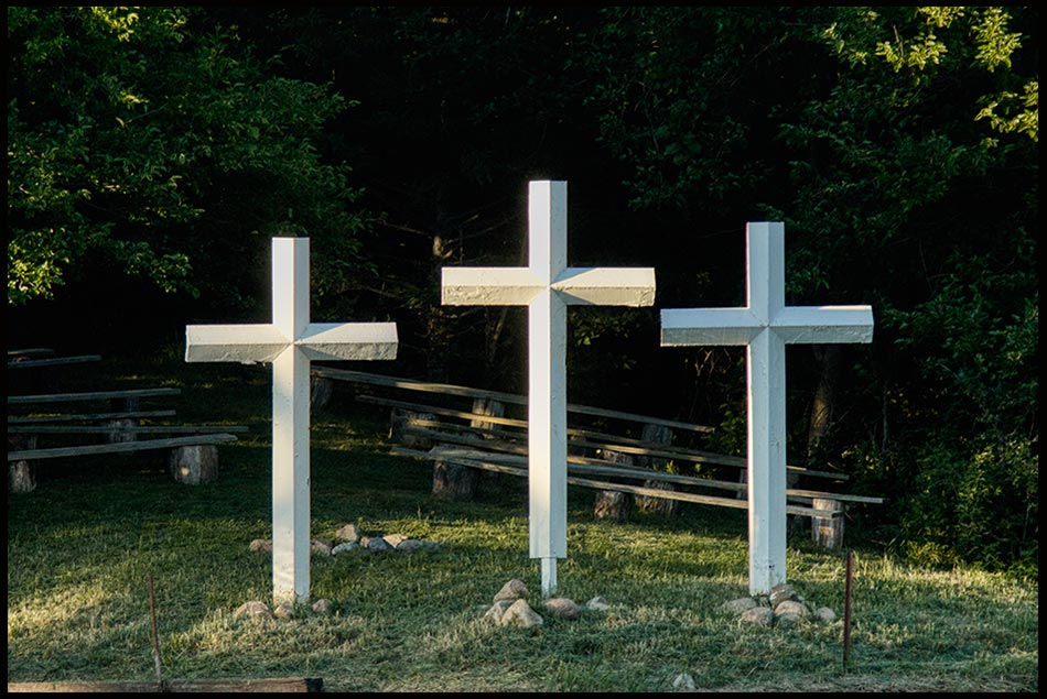 Three white crosses with the sun hitting the middle one. Bible verse Matthew 27:59-60 was and instrument of death and torture. Christ has transformed into a symbol of hope and redemption.
