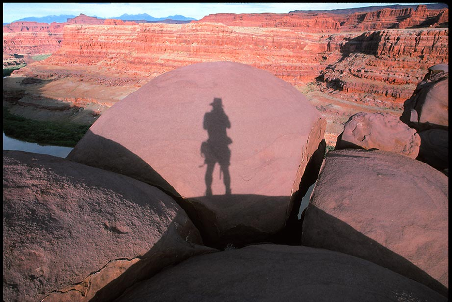 A photographers shadow on rounded boulders, Canyon Lands National Park, Utah and Bible verse Psalms 102:11-12 Fade lake a shadow