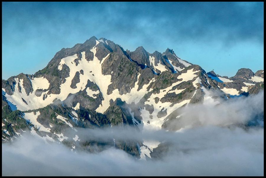 Mount Carrie of the Olympic Range between layers of clouds, Olympic National Park, Washington State Mountains and the confidence of God