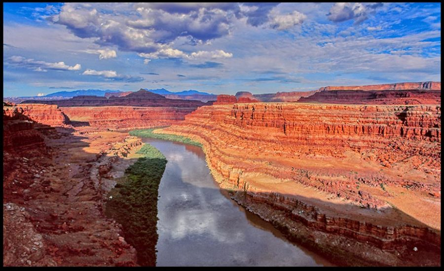 Puffy clouds and blue sky and red cliffs above the Green River from the White Rim Road, Canyon Lands National Park, Utah and Isaiah 41:18 Bible verse Springs in the Midst.
