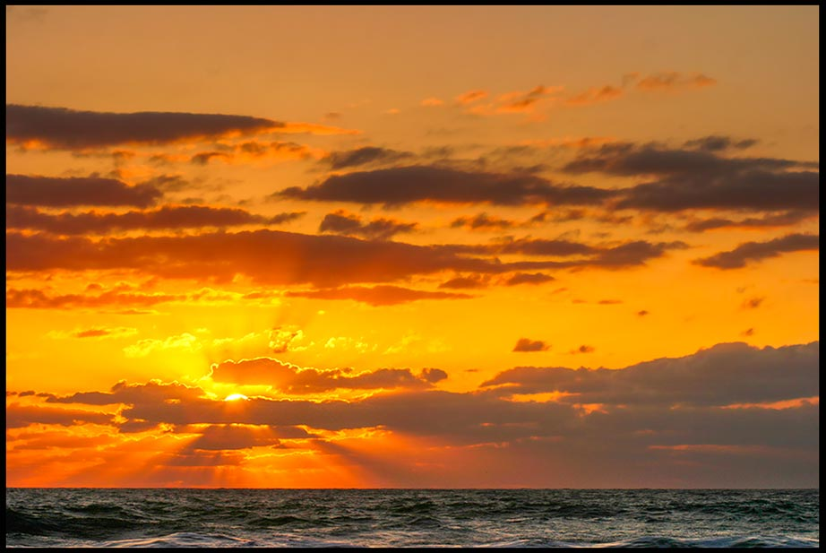 Sun beams break through clouds at sunrise over the Atlantic Ocean at Melbourne Beach, Florida and John 3:16-18. Bible Verse God so loved