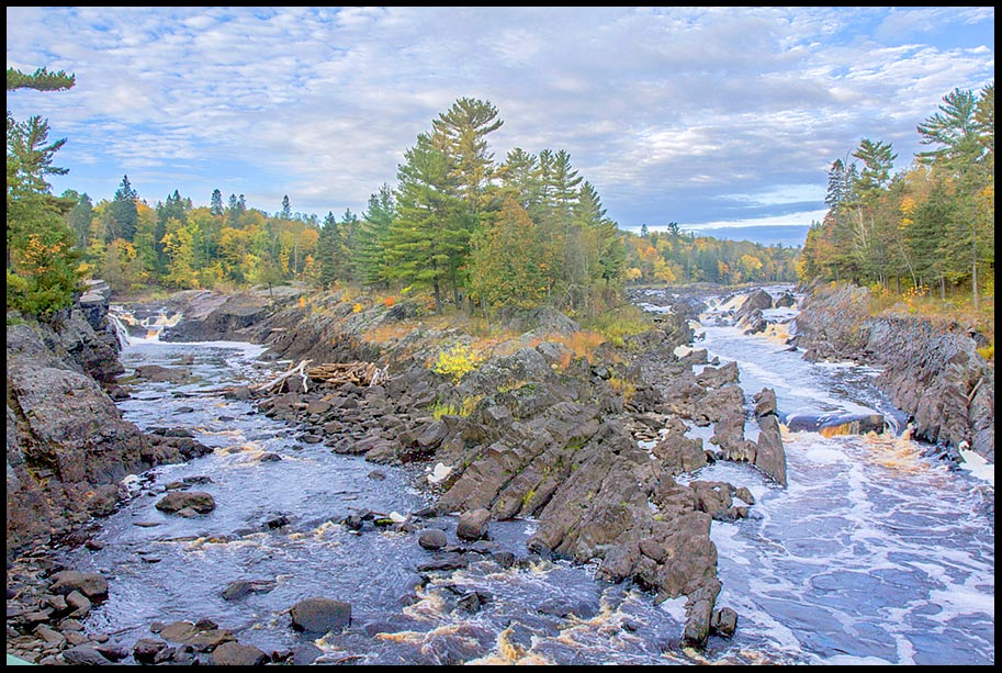 Water flows around a rock island in the Saint Louis River, Jay Cooke State Park, Minnesota and Psalm 25:6-7 Bible Verse God's mercy flows over us