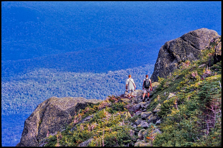 Two hikers Pass two large boulders as they head towards the Great Gulf, White Mountains, New Hampshire. Bible verse of the day, Deuteronomy 1:21 Take possession