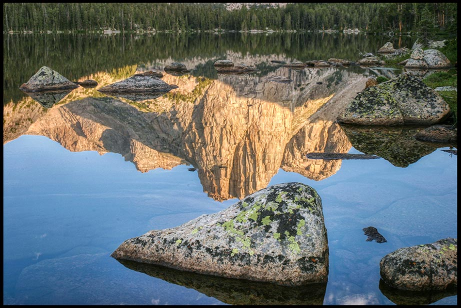 Mountains and a blue sky reflect next to a rock in Middle Cathedral Lake, Wind Rivers Wilderness, Wyoming and Bible verse Psalm 103:21-22 Works of His