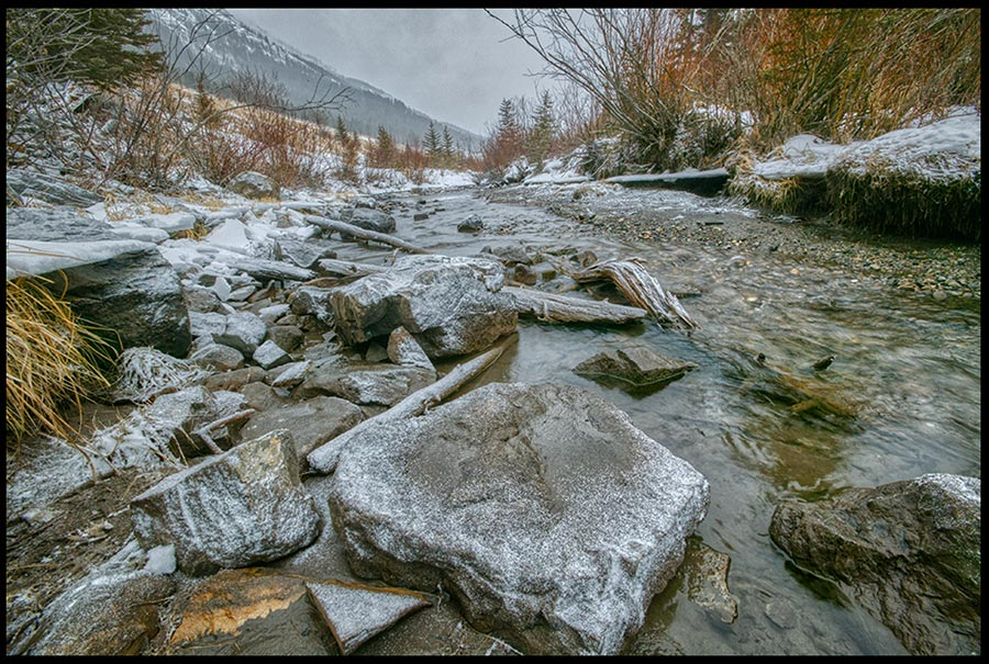 Small snow flakes cover a rock in thawed mountain stream in late Winter Alberta, Canada. Bible Verse of the Day Psalm 147:18 frozen hearts