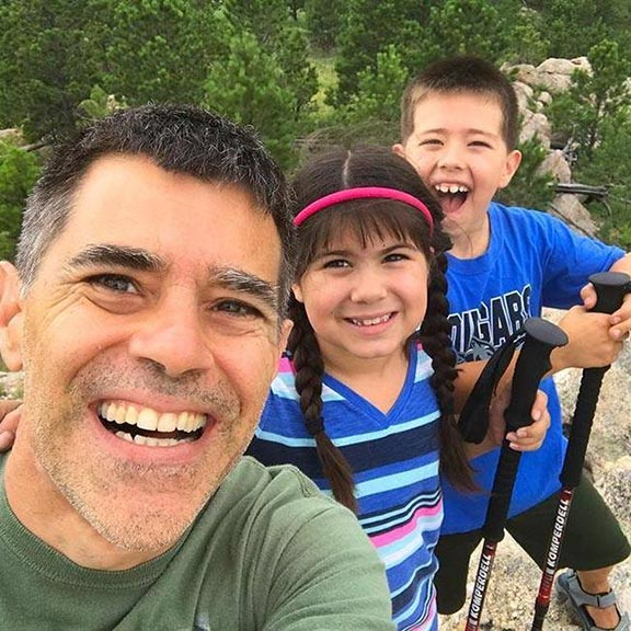 A man (father) and children take a selfie on a rocky hilltop in the Black Hills, South Dakota for the website The Visual Bible verse of the Day