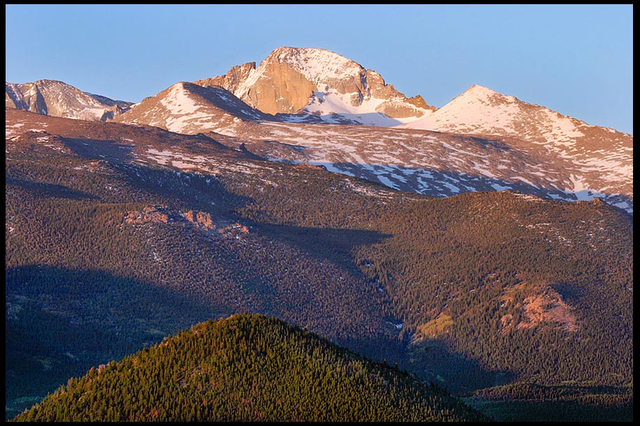Snow covers parts Longs Peak on clear morning with a bright blue sky, Rocky Mountain National Park, Colorado and Psalm 65:8 Bible verse filled with Awe