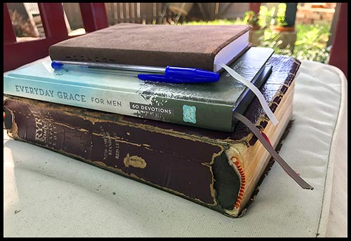 A stacked Bible, devotional journal and pen on a bench in a secret garden