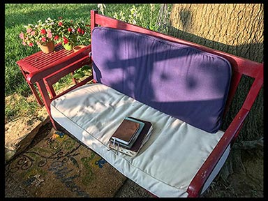A red bench with a Bible, journal and devotional on it in a secret garden