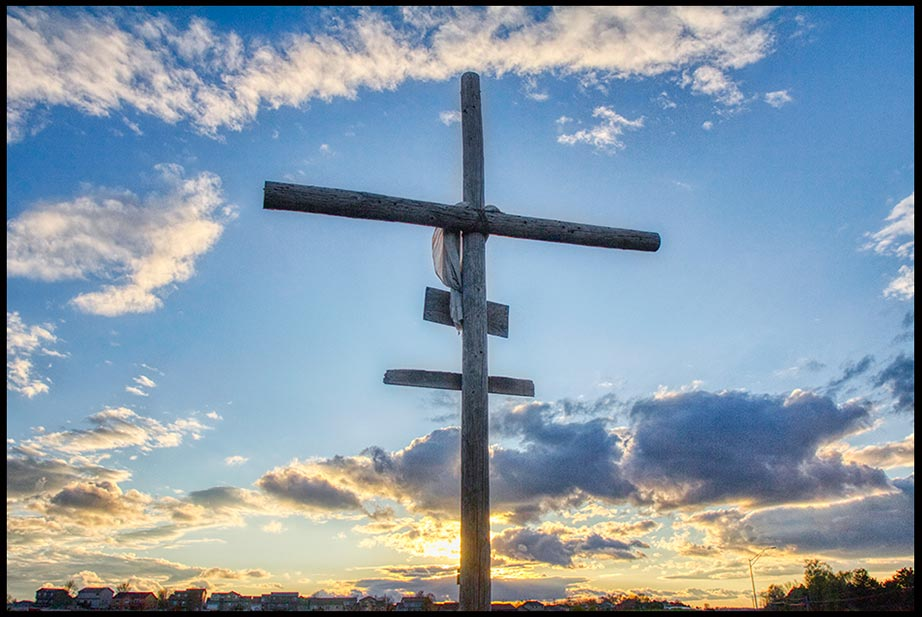 A cross silhouetted against a blue sky and white clouds near sunset, Papillion, Nebraska Bible Verse of the Day: Mark 8:34, 35. Christ call us to take up our Cross