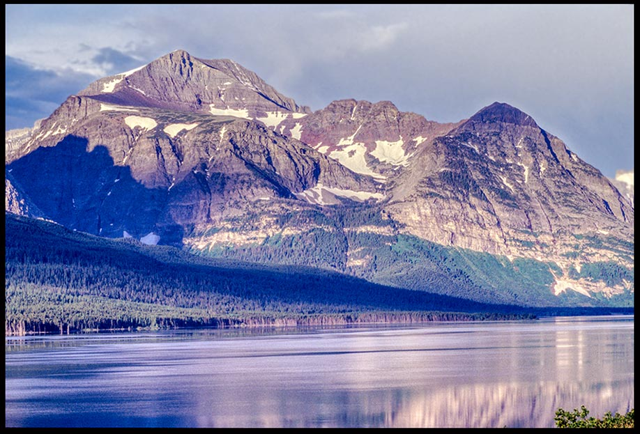 The granite mountains with snow along Lake Sherburne, Glacier National Park, Montana The attributes of God and Bible Verse of the Day: Isaiah 46