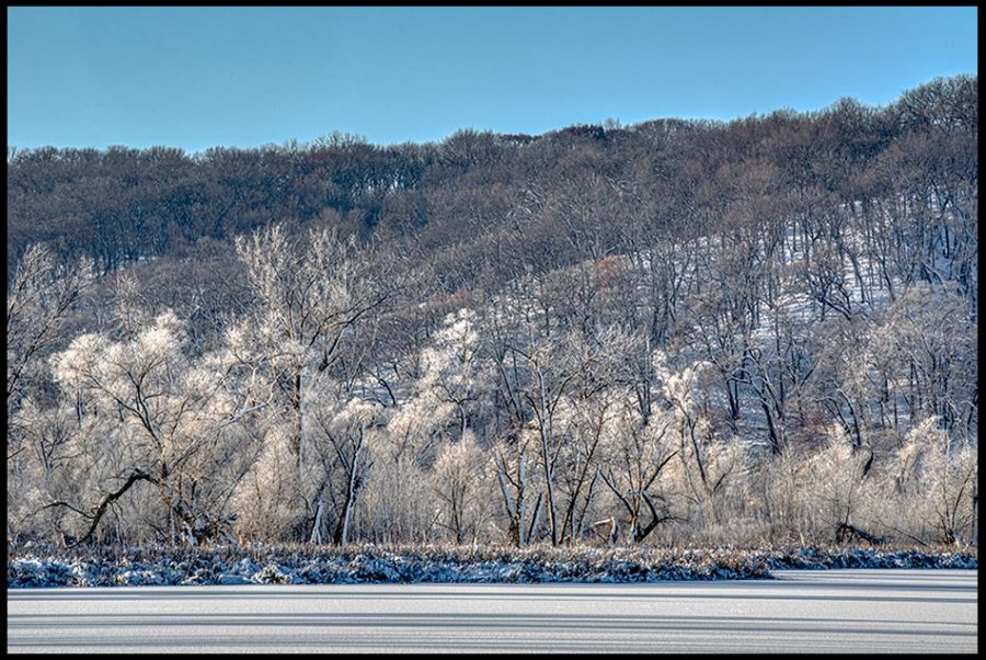 A frozen lake below hill covered with snow and hoarfrost covered trees, Fontenelle Forest, Nebraska. Bible Verse of the Day: Job 38:29-30 God and His greatness