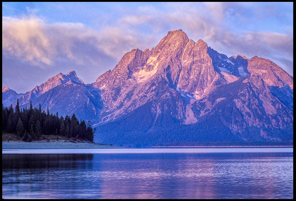 The alpine glow hits Mount Moran on the shore of Jackson Lake as seen from Coulter Bay, Grand Teton National Park. Bible verse 145:10-12, God's Might acts