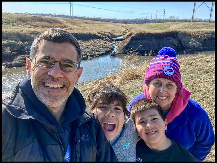 A outdoor selfie of a family of four (a mom and dad with their son and daughter). Head to the outdoors to free your anxiety from covid-19