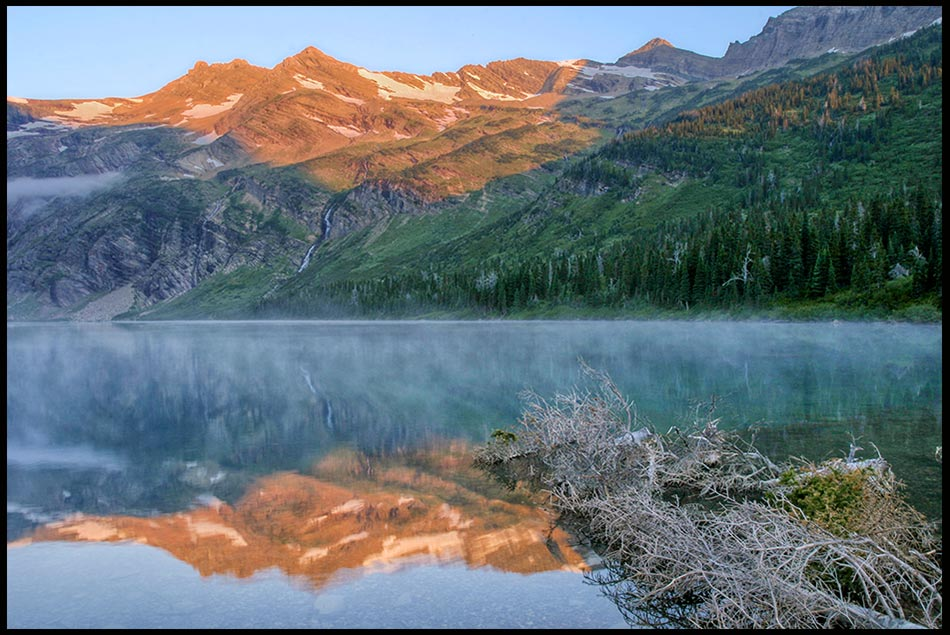 The alpine glow on mountains reflect in Gunsight Lake at dawn in Glacier National Park, Montana and Psalm 145 about God's mighty works.