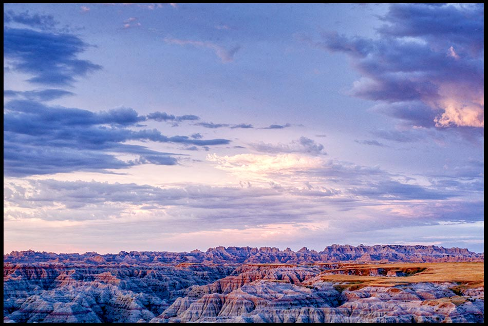 Blue, white and red clouds in the predawn sky over dessert rock formations in the Badlands National Park, South Dakota and Psalm 68:34. Bible verse about God strength in the skies