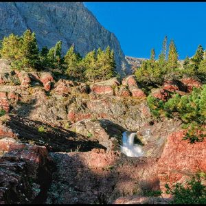 A Small portion of redrock Falls waterfalls seen amongst the rocks in Glacier National Park and Bible Verse Psalm 78 15 16 Moses and water from the rock