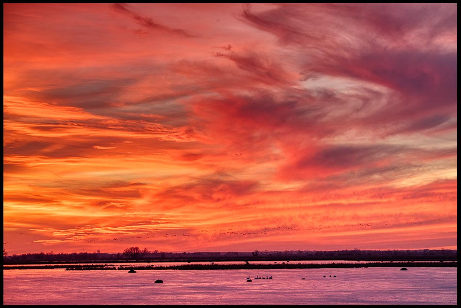 Red sunset sky with whispy clouds over the lake at Loess Bluffs Wildlife Refuge National Wildlife Refuge, Missouri. Bible Verse of the Day: Psalm 57:10-11
