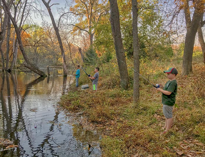 Boys fishing on Duck Creek under trees in fall colors, Duck State Park, Nebraska.