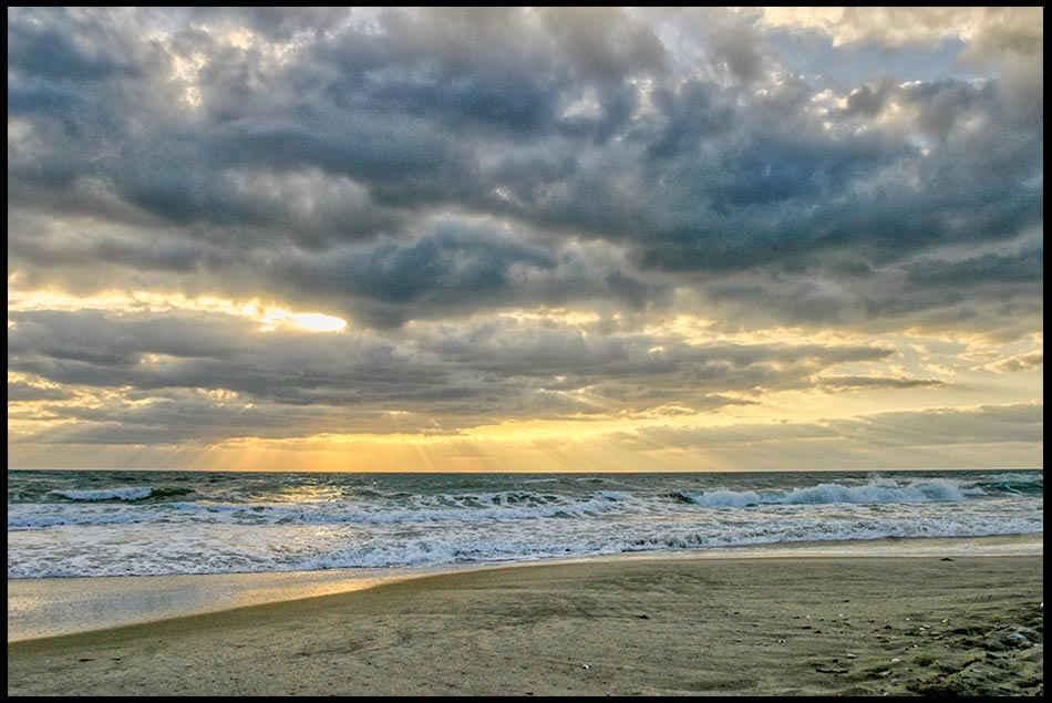 The Sun barley breaks through a mostly cloudy sky over white capped waves along the shore of Melbourne Beach Florida. Bible verse of the day the wind and the waves. Psalm 107:24–25